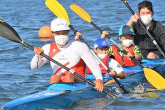 競技人生の原点の御所湖で児童と一緒にカヌーをこぐ水本圭治選手(左)=2日、盛岡市繋