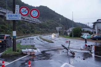 地震の影響で道路に倒れた信号機と傾いた道路標識=6日午前5時51分、岩手町