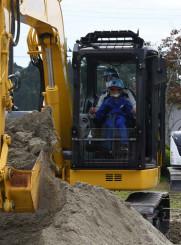 重機のショベルを操作し、砂を掘り起こす室根西小の児童