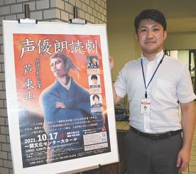 朗読劇のポスターと並び、「東山の魅力発信につながる」と語る三浦隆史さん