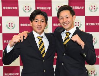 肩を抱き、喜びを分かち合う東北福祉大の大里昂生(右)と三浦瑞樹=仙台市・同大トレーニングセンター