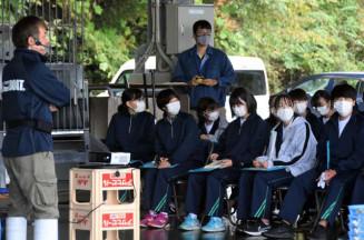 佐々木淳さん(左)から水産業の現状の説明を受ける盛岡三高の生徒たち