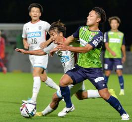 激しく競り合う岩手のFW色摩雄貴(手前左)。安定感を増した攻守でチームの躍進を支える=9日、盛岡市・いわぎんスタジアム