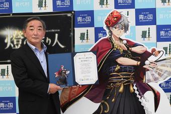 陸中黒崎灯台のキャラクターの贈呈目録を手にする柾屋伸夫村長