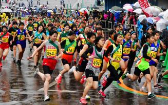 冷たい雨が降りしきる中、たすきをつなぐために勢いよく走りだす中学校女子の選手たち=15日、盛岡市・県営運動公園陸上競技場