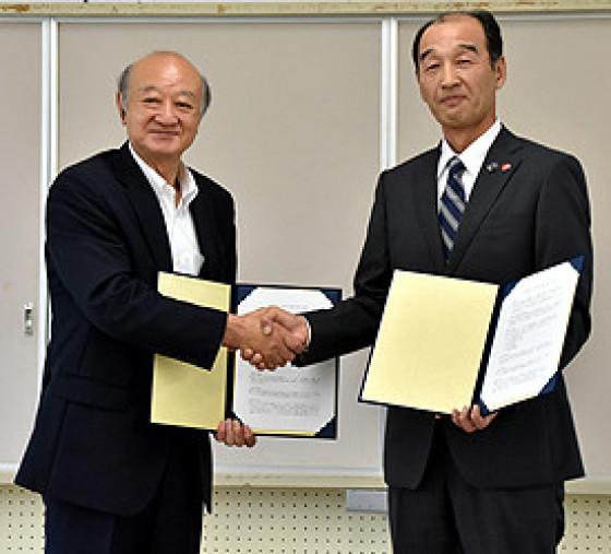 調印を交わし協定書を掲げる伊達勝身町長(左)と成田健二執行役員営業本部副本部長