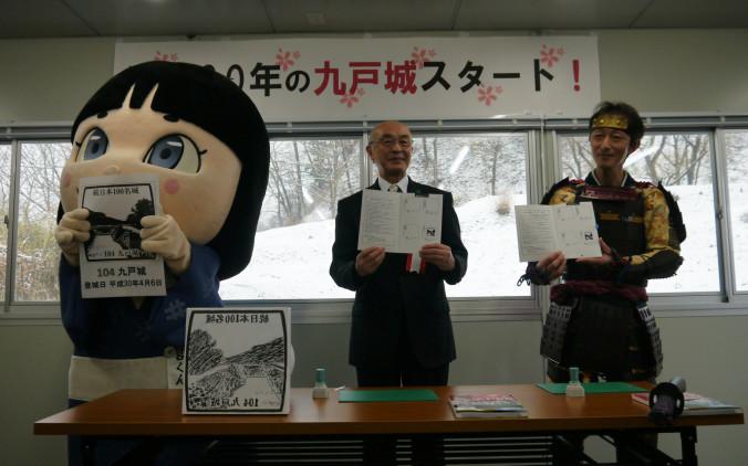 「九戸城スタート!」セレモニーで押したスタンプを見せる(左から)亀麿くん、鳩岡矩雄市教育長、九戸政実武将隊の佐藤貴之隊長