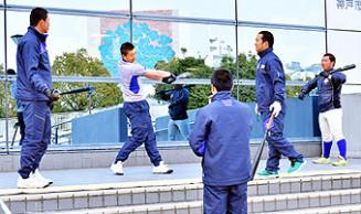 ガラスに映る自身のフォームを確認しながら素振りに励む盛岡大付の選手=神戸市内