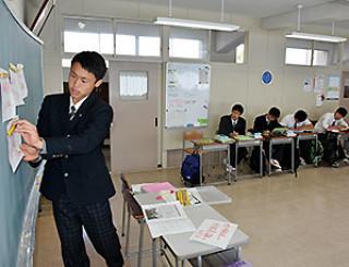 黒板に紙を張りながら意見を述べる生徒