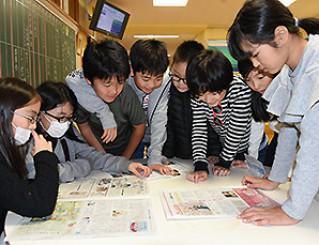 「読ん読コーナー」で新聞を広げ、コーナーの活性化について話し合う岩手大付属小5年たけ組の児童