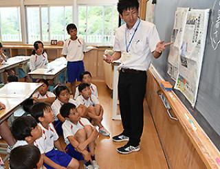 「真夏日」と「猛暑日」を報じる岩手日報の記事を読み比べる大槌学園5年1組の児童