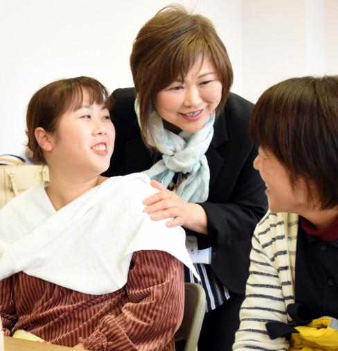 スタイリングや化粧を終えて高山恵子支部長(中央)と話す参加者(左)