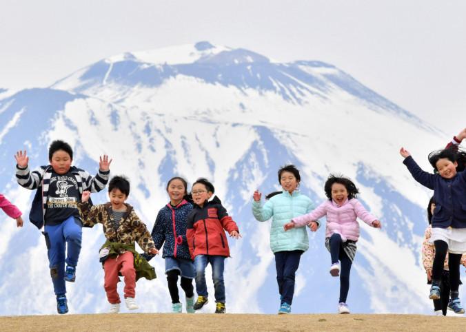 雪解けで現れた岩手山の「ワシ形」。雄大な山を背に子どもたちの歓声が響く=14日、盛岡市向中野・盛岡南地区公園
