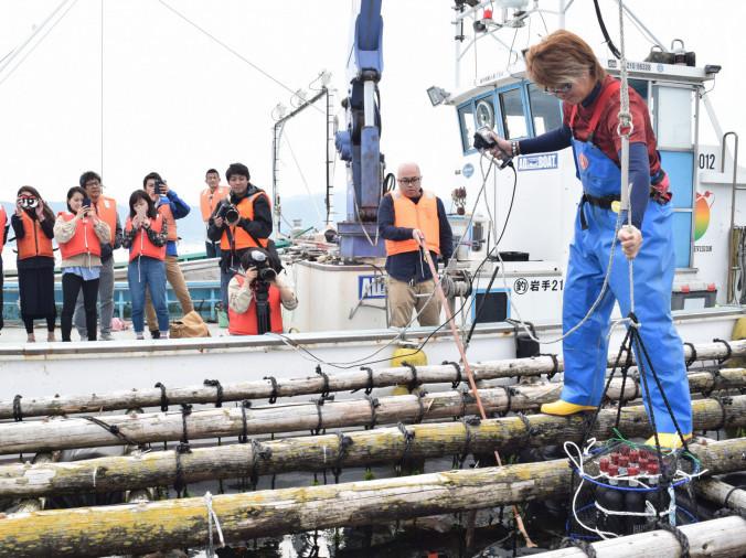 海中に酒を沈める作業を見守る参加者
