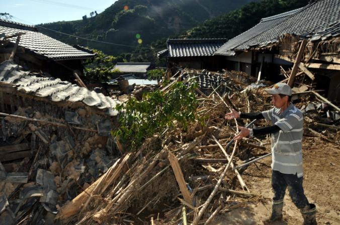 崩落した土砂が直撃した二宮健三さんの住家。人手不足もあって自宅の復旧には手を付けられず、道路の泥出しに精を出す=12日、愛媛県宇和島市吉田町