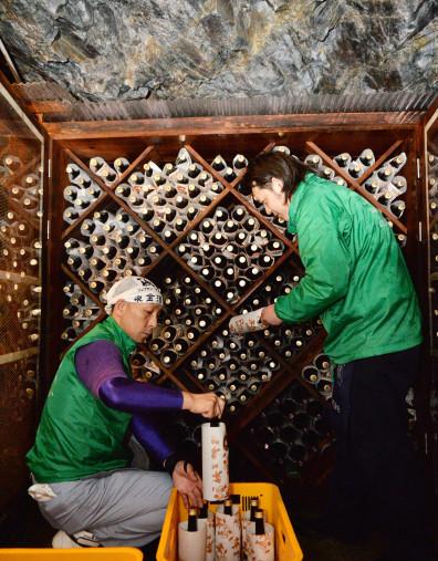 龍泉洞内の貯蔵所に日本酒を並べる泉金酒造の従業員