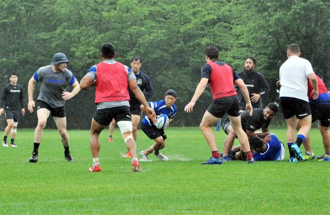 雨の中、精力的に攻守の連係を確認するSH高城佑太(中央)らパナソニックの選手=12日、八幡平市ラグビー場