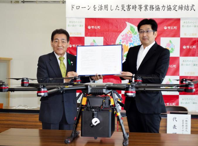 協定書を取り交わす深谷政光町長(左)と佐藤亮厚代表理事