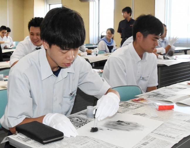 特殊な粉末を使って指紋の採取を体験する参加者