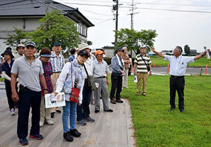 市埋蔵文化財調査センターの佐久間賢所長(右)に案内されながら、胆沢城跡を散策するバスツアー参加者