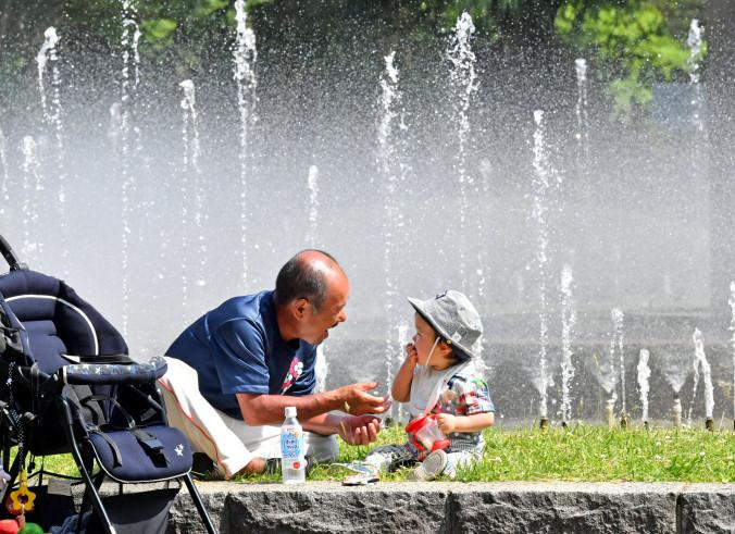 強い日差しの中、噴水の前で戯れる佐々木一夫さん(左)と孫の村山隼翔ちゃん=7日、盛岡市みたけ・県営運動公園