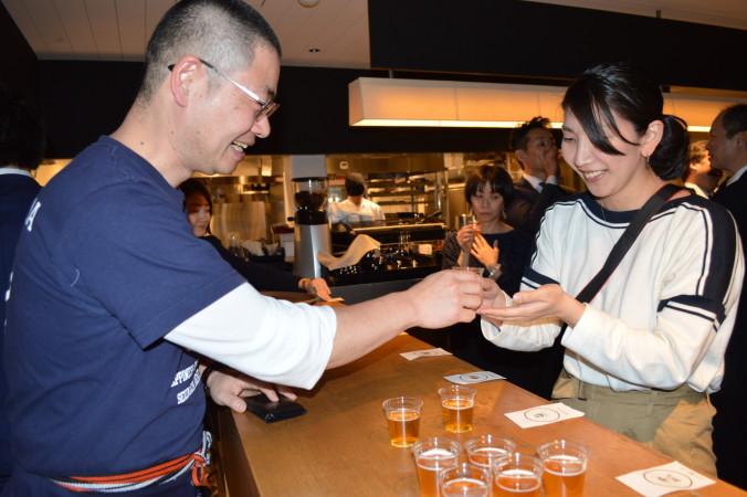 来場者に新ビール「東北魂的IPA」の試飲を勧める佐藤航社長(左)