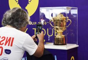 ラグビーW杯の優勝杯「ウェブ・エリス・カップ」を写真に納める男性=27日午前、岩手県釜石市