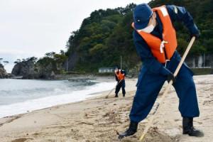 東日本大震災の行方不明者の手掛かりを求め、砂浜の捜索をする警察官=9日午前、岩手県普代村