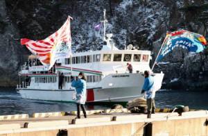 大漁旗に迎えられるみやこ浄土ケ浜遊覧船の最終便=11日午後、岩手県宮古市