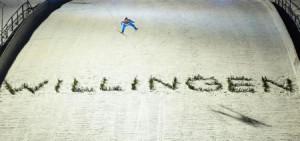 ーW杯ジャンプ男子個人第16戦、「ビリンゲン」の文字を飛び越えるハルボルエグネル・グラネル=30日、ビリンゲン(AP=共同)