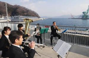 岩手県釜石市で、海に向かって復興支援ソングなどを演奏する市民吹奏楽団=7日午後