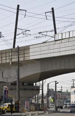 地震の影響で傾いた東北新幹線の架線を支える電柱=14日午前11時48分、福島県郡山市