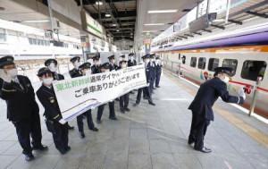 東北新幹線が通常ダイヤに復帰し、JR東京駅のホームで横断幕を掲げて乗客を見送る駅員ら=26日午前