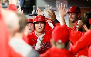 マリナーズ戦の1回、46号となる先頭打者本塁打を放ち、ベンチで迎えられるエンゼルス・大谷=シアトル(共同)